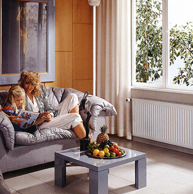 Historic advertisement for Kermi radiators - mother and child in living room